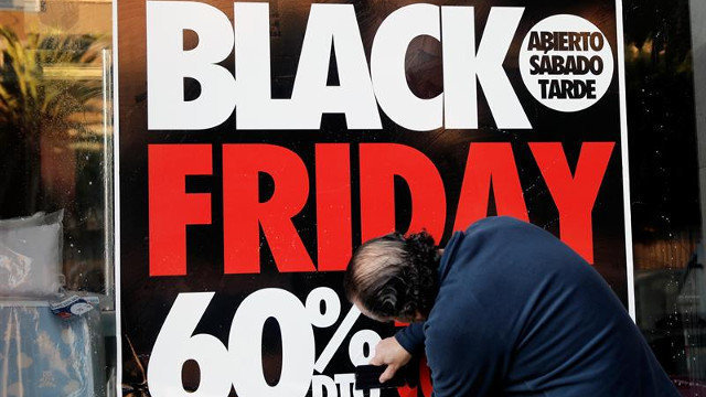 Un home coloca un cartel do Black Friday. JUAN CARLOS CÁRDENAS (EFE)